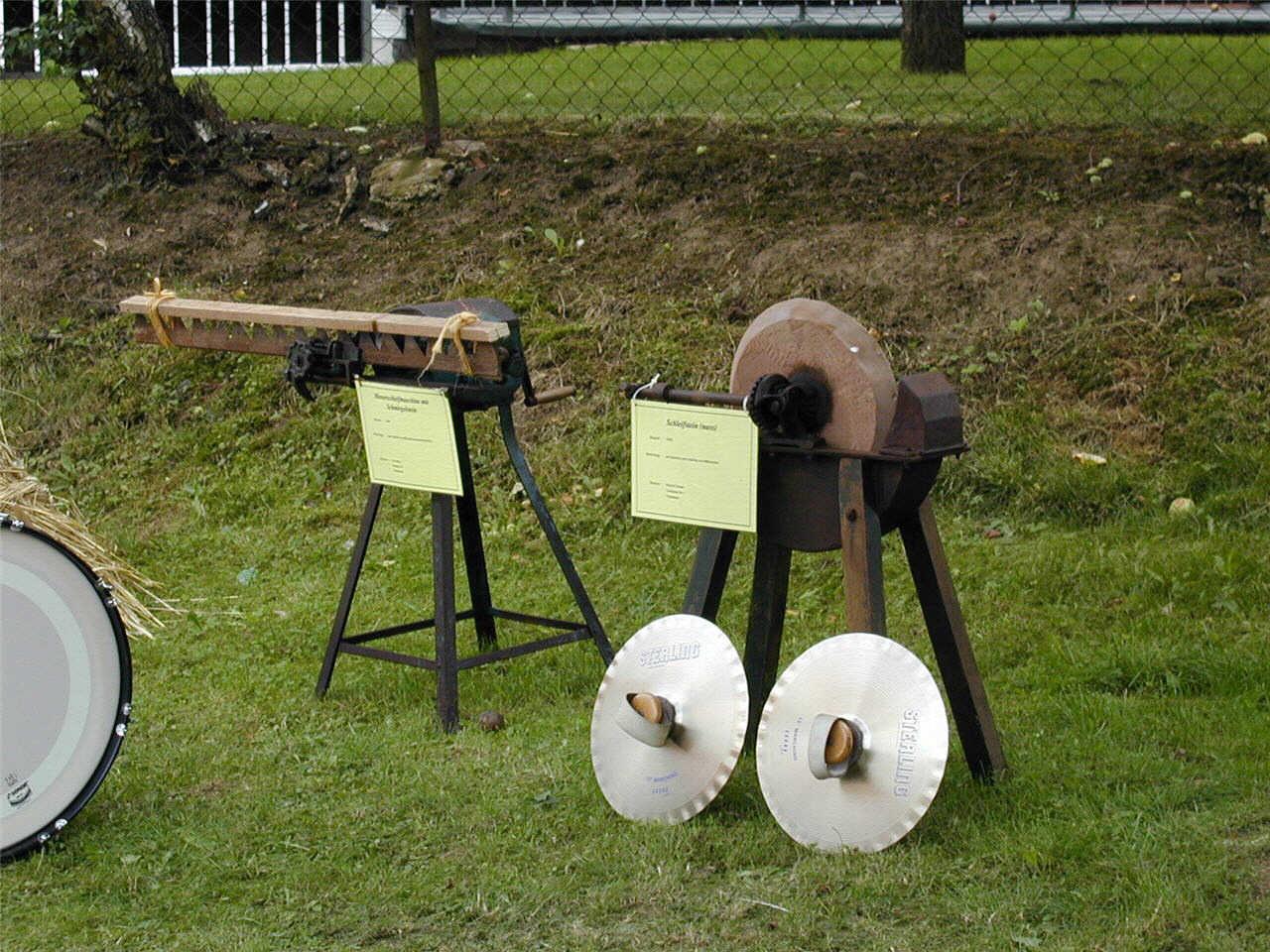 Alte Maschinen von links: Halbautomatischer Schleifstein für Mähmesser vom Balkenmähwerk, daneben ein Schleifstein aus Sandstein. (© Detlef Battefeld)