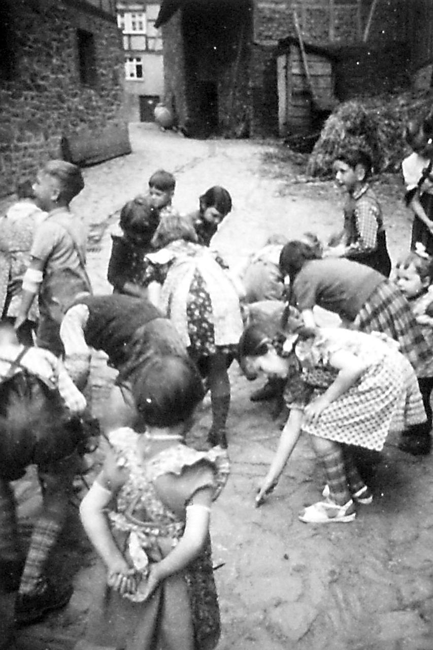 """Kinder beim Geld """"Grabschen"""" aufsammeln auf Diehlen Hof, Stockweg. (© Stadt Frankenberg Eder)"""