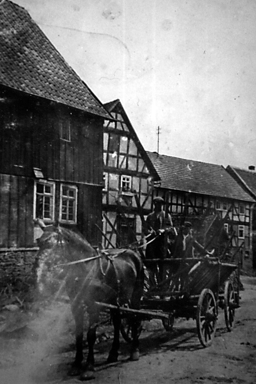 """Bauer Heinrich Lückel auf dem Weg ins Feld vor den Häusern """"Stuhlmann"""" (abgerissen), """"Gallen"""" (abgerissen) und """"Schäferchrist"""" (alt). (© Stadt Frankenberg Eder)"""