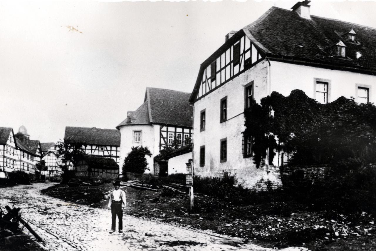 Dorfstraße um 1906, Peter Battefeld (Gloren) auf dem Foto zu sehen, ältestes Bild der Dorfstraße mit dem alten Backhaus (Trillofen, zur Behandung der Dedequenten). (© Stadt Frankenberg Eder)