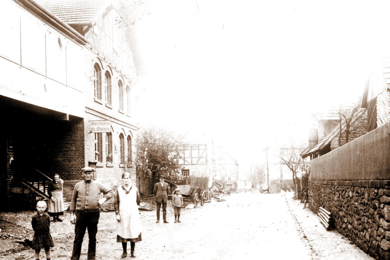 Gasthaus Thiele und Dorfstraße um 1932 (von links: unbekannt, Katharina Thiele/Rohde, Fritz Thiele senior, Elisabeth Küthe/Isgen, Fritz Thiele junior, unbekannt; im Fenster rechts: Karl Thiele). (© GasthofThiele)